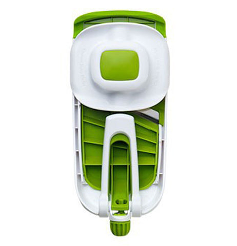 Green and white vegetable slicer folded for compact size.