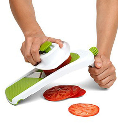 Green and white vegetable slicer in use slicing tomatoes.