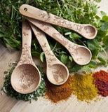 The four measuring spoons are shown lying on top of some vegetables with a few different spices lying underneath them.