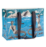 Blue tote bag with black shoulder handles and images of mermaids sitting on rocks watching whales and dolphins swimming nearby.