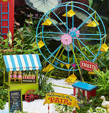 "The white pebbles are shown as the base for a miniature fair setting, which includes a food stand, ticket stand, ferris wheel, and a ""Welcome to the Fair"" sign."