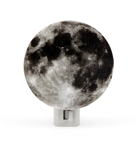 A nightlight in the shape of the moon colored black, gray, and white.