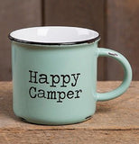"This cyan ""Happy Camper"" mug is sitting on a wooden table and has a wooden background"
