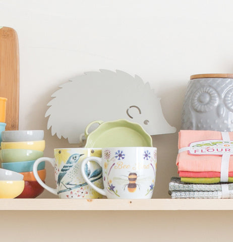 a mug with a beee on it sits on a shelf along side a hedgehog trivet and a couple of small bowls