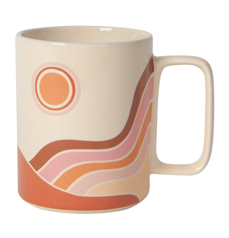 "Front view of ""Solstice"" white ceramic mug with red, orange, and pink sun, rainbow, and sand dune design on a white background."