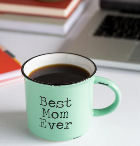 "The mint green mug with the words, ""Best Mom Ever"" is shown sitting on a table with some coffee inside it."