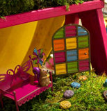 The multi-colored panel door is shown next to a pink bench in a small fairy garden setting.
