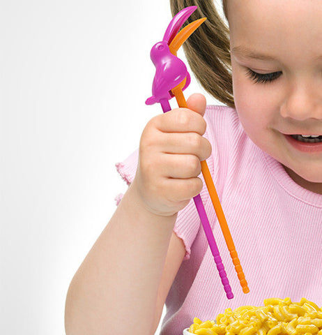 A little girl using the toucan shaped chopsticks for her noodles