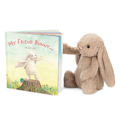Front cover of My Friend Bunny book slightly open standing up next to a stuffed bunny.