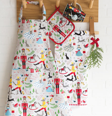 The nutcracker apron is shown hanging from a hook on a wall next to a potholder and tablecloth that also have a nutcracker design on them.