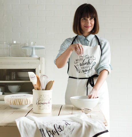 "A woman wears the apron that says, ""Where There's a Whisk, There's a Way"" as she works in the kitchen."