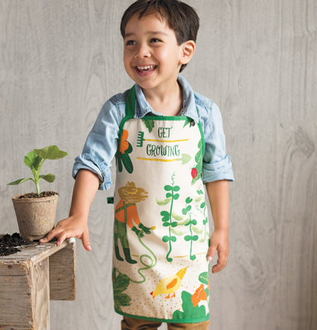 "A little boy is shown wearing the green ""Get Growing"" apron."
