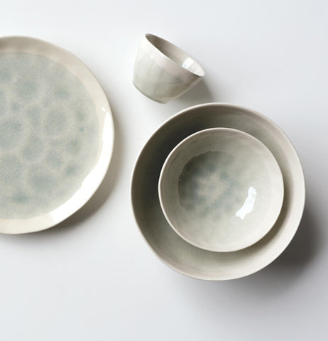 "Cream and gray ""Aquarius"" serving bowl that has a cream and gray bowl nested in it with a cup and plate laying next to them."