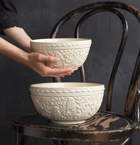 "The large Heirloom ""Flock Together"" Mixing Bowl is sitting on an old worn black wood chair while the small heirloom flock together bowl is being held by someone who is placing it inside the larger one, both are all white with a raised texture pattern that features flowers and birds taking up the main body and a rope pattern around the top"