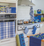The blue and white striped dish towel is shown hanging from the handle of an oven door in a kitchen.