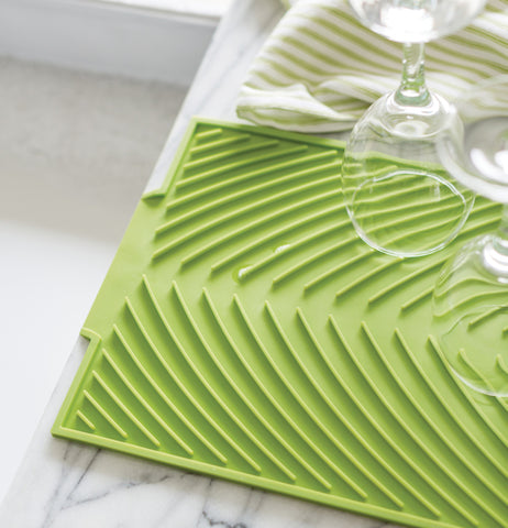 Some wine glasses are shown drying on the green drying mat.