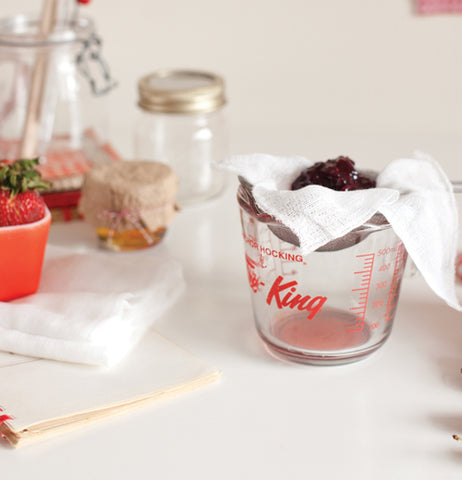 The cheesecloth is shown holding strawberries in a measuring cup.