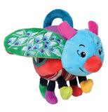 This small stuffed toy is of a bug with a purple and red body, black legs, a blue head with pink antennae, a red nose, and green wings with purple spots. A dark blue ring is at the top of the bug's body.