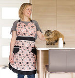 Lady wearing her cat's meow apron standing next to a table while petting a brown cat.
