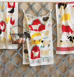 Three dishtowels with simple representations of farm animals, barns, and fences hanging from a rack with a basket of eggs.