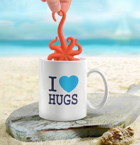 "A hand is putting the ""Octeapus"" Tea Infuser into a mug that says ""I heart Hugs"" at the beach."