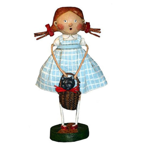 This figurine is of Dorothy holding her brown basket with Toto the little black dog inside it.  She is wearing her blue and white sleeveless dress.