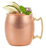 Copper mug has a handle that is a cool shape and has limes in it.