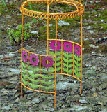 Mini orange Gazebo with green stems and purple flowers.