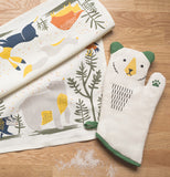 The white and green bear shaped oven mitten is shown lying on a wooden table next to a placemat and napkin.