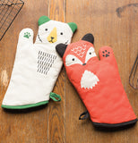 The white and green bear shaped oven mitten is shown lying on a wooden table next to a red mitten shaped like a fox.
