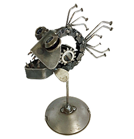 A sculpture of a piranha is made out of recycled metal. It's attached to a small circular platform with a pole. The piranha is facing the left corner.