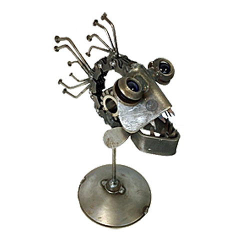 A sculpture of a piranha is made out of recycled metal. It's attached to a small circular platform with a pole. The piranha is facing the right corner.