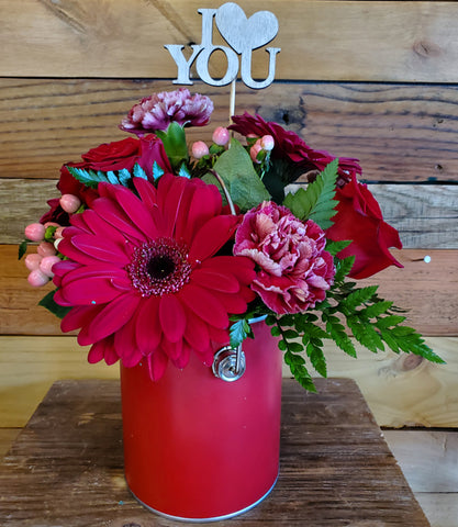 "A red and purple bouquet of flowers in a red vase. There is a silver colored cardboard insert that says ""I love you."""