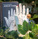 The Palm Reader Jewelry Stand and its packaging both sit in a garden.