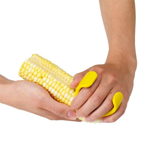 A yellow corn cutter that contours the shape of the hand with sharp blades.
