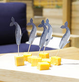 The picks with the narwhal cutouts are shown sticking into some pieces of cheese.