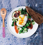 "The spoon with the words, ""Pass it On"" is shown sitting on a table next to some eggs, steak, and broccoli."