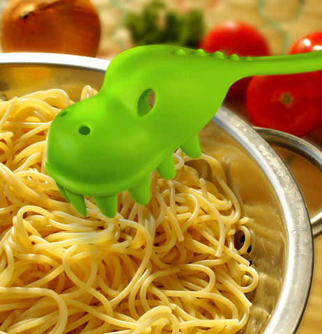 A green dinosaur shaped pasta serving spoon ready to be used in a bowl of pasta