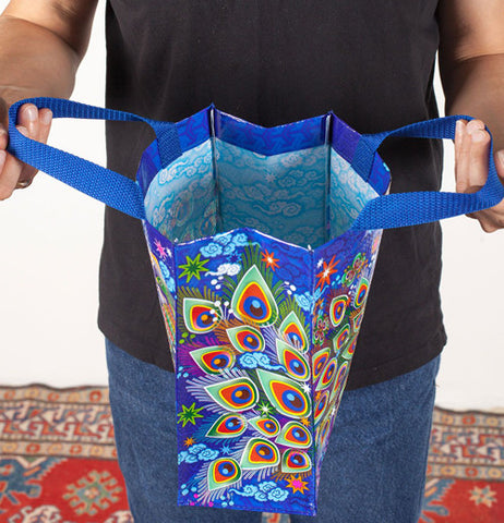 Person holding open a blue shopper bag with a colorful peacock feather design pattern shown from the side.