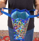Person holding open a blue handy tote bag with beautiful peacock feather design on the side.