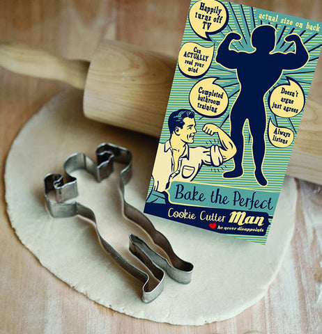 The silver cookie cutter shaped like a muscular man is shown next to its blue box sitting on some cookie dough flattened under a rolling pin.