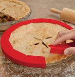A picture of a person's hand placing the pie shield on the pie.