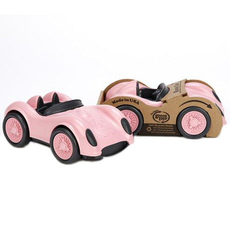 a light pink race car with black wheels and accents alongside the same car in its original packaging