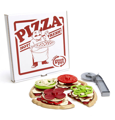 a bunch of plastic play pieces in the shape of cheese, tomatoes, onions, and other various pizza toppings stacked on pizza slices with a grey pizza cutter next to it with a pizza delivery box standing up behind the play pizza