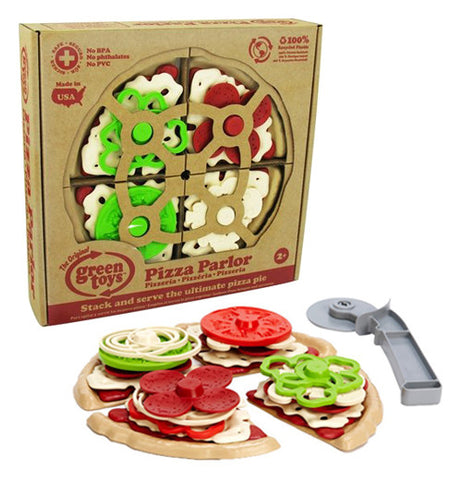 a bunch of plastic play pieces in the shape of cheese, tomatoes, onions, and other various pizza toppings stacked on pizza slices with a grey pizza cutter next to it and the same items in their original packaging sitting behind them