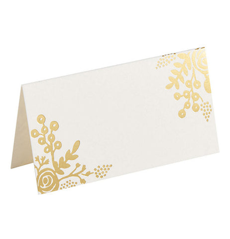 A placecard decorated with a gold foil floral pattern in two corners.