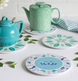 A white edge with a light blue center Meadowland plate that contains two shades of blue animals with the two types of tea pots and plates on a white table