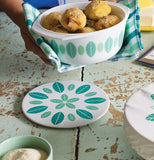 "Person holding a trivet ""Planta"" stoneware white bowl over a blue/green gingham kitchen towel and white plate both with green leaves on a sea green distressed wooden table"