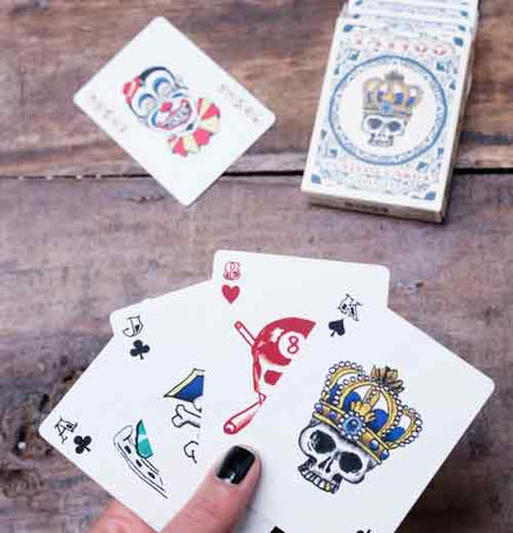 Hand holding King of spades card with skull wearing crown, Ace of hearts with red skull and crossbones, a jack of clubs, and an Ace of clubs are also in the hands over a brown wood table. The deck of cards with the king of clubs with skull and crown design next to the joker card with red, blue, and yellow circus clown design are on the table.
