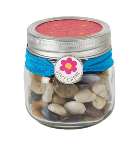 Shiny rocks in a pint size jar with blue ribbon tied around the top and has a flower.